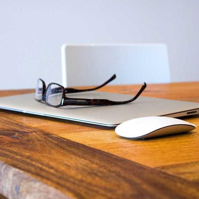 Glasses and laptop on table
